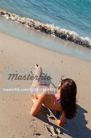 Female in bikini sitting on the wet sand in front of the ocean Stock Photo - Premium Royalty-Free, Image code: 6109-06006242