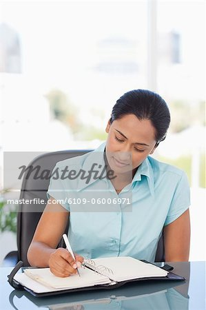 Relaxed secretary ar work is writing on her dairy while sitting at a desk Stock Photo - Premium Royalty-Free, Image code: 6109-06006971