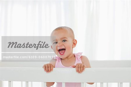 Little baby shouting loudly while standing up in her bed Stock Photo - Premium Royalty-Free, Image code: 6109-06007023