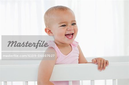 Little baby laughing while standing up in her white bed Stock Photo - Premium Royalty-Free, Image code: 6109-06007027