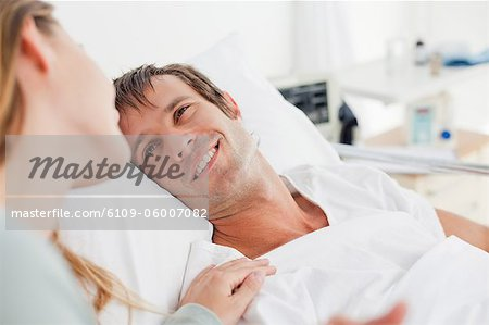 Smiling patient looking at his girlfriend while lying in a hospital bed Stock Photo - Premium Royalty-Free, Image code: 6109-06007082