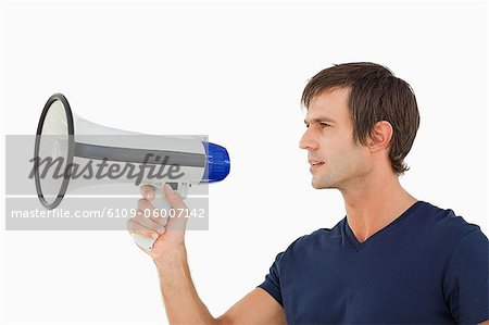 Serious man holding a megaphone while looking away against a white background Stock Photo - Premium Royalty-Free, Image code: 6109-06007142