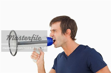 Furious man shouting through a megaphone against a white background Stock Photo - Premium Royalty-Free, Image code: 6109-06007143