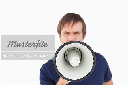 Furious man shouting while using a megaphone against a white background Stock Photo - Premium Royalty-Free, Image code: 6109-06007144
