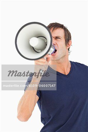 Furious man using a megaphone while shouting against a white background Stock Photo - Premium Royalty-Free, Image code: 6109-06007147