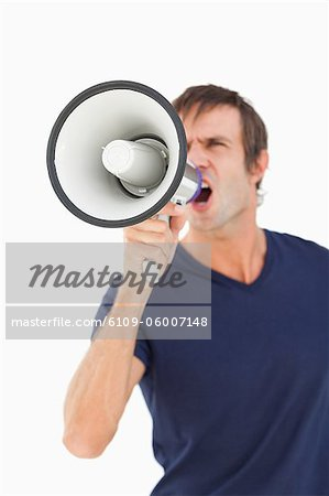 Megaphone held by a furious man against a white background Stock Photo - Premium Royalty-Free, Image code: 6109-06007148