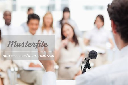 Businessman making a hand gesture as he gives a speech to a group of his colleagues Stock Photo - Premium Royalty-Free, Image code: 6109-06007236