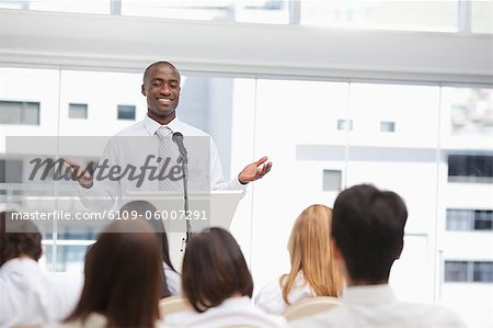 Businessman smiling as she gestures with both hands towards an audience Stock Photo - Premium Royalty-Free, Image code: 6109-06007291