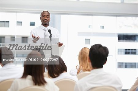 Businessman gesturing with his hand towards an audience who are watching him Stock Photo - Premium Royalty-Free, Image code: 6109-06007297