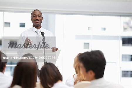 Smiling businessman gestures towards an audience who are watching him Stock Photo - Premium Royalty-Free, Image code: 6109-06007298