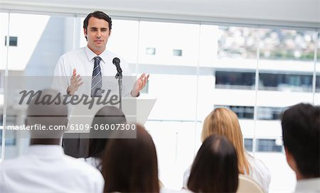 Black haired businessman gestures towards an audience who are watching him Stock Photo - Premium Royalty-Free, Image code: 6109-06007300