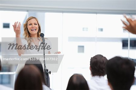 Businesswoman laughing as she gestures to a member of an audience who has his arms raised Stock Photo - Premium Royalty-Free, Image code: 6109-06007302