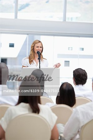 Businesswoman smiling as she looks to the side while an audience is watching her Stock Photo - Premium Royalty-Free, Image code: 6109-06007303