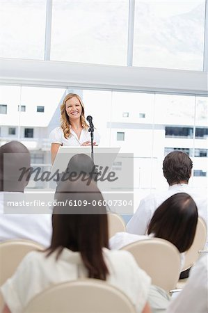 Woman smiling as she looks ahead at an audience who are watching her Stock Photo - Premium Royalty-Free, Image code: 6109-06007304