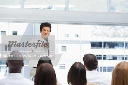 Businessman sorting out his tie as he is being watched by an audience Stock Photo - Premium Royalty-Free, Image code: 6109-06007307