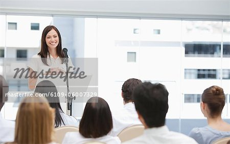 Brunette businesswoman giving a speech while she is being watched by her colleagues Stock Photo - Premium Royalty-Free, Image code: 6109-06007329