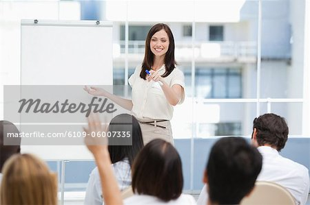 Woman smiling as she gestures to a member of the audience that has her hand raised Stock Photo - Premium Royalty-Free, Image code: 6109-06007335