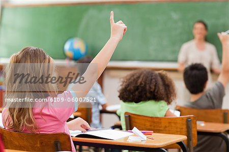 Back view of little girl raising hand in class Stock Photo - Premium Royalty-Free, Image code: 6109-06007521