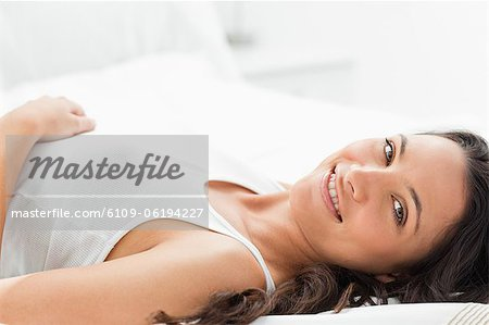 Delighted woman smiling in her bed Stock Photo - Premium Royalty-Free, Image code: 6109-06194227