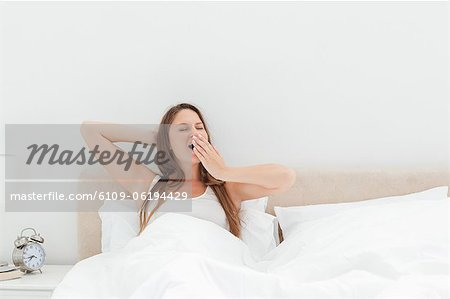 Cute woman yawning in her bed Stock Photo - Premium Royalty-Free, Image code: 6109-06194429