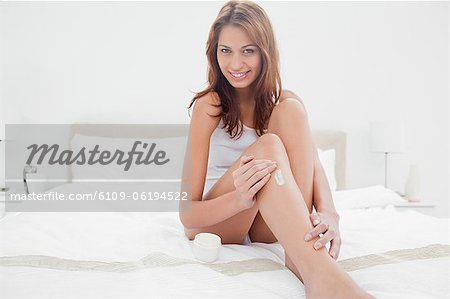 Portrait of a smiling woman applying moisturizer Stock Photo - Premium Royalty-Free, Image code: 6109-06194522