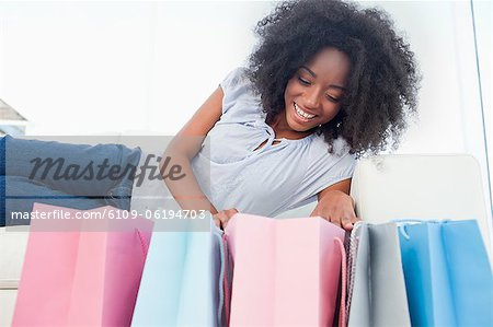 Happy fuzzy hair woman looking into her shopping bags Stock Photo - Premium Royalty-Free, Image code: 6109-06194703