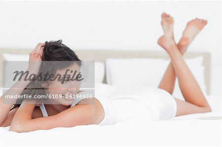 Beautiful woman on her bed Stock Photo - Premium Royalty-Free, Image code: 6109-06194936