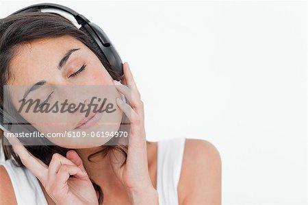Close-up of a brunette enjoying music Stock Photo - Premium Royalty-Free, Image code: 6109-06194970