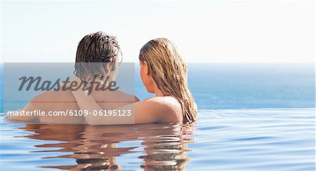 Back view of couple spending time in the pool Stock Photo - Premium Royalty-Free, Image code: 6109-06195123