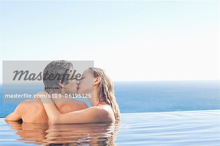Back view of kissing couple in the pool Stock Photo - Premium Royalty-Free, Image code: 6109-06195125