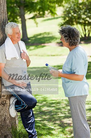 Man in running gear is leaning against a tree talking to a woman Stock Photo - Premium Royalty-Free, Image code: 6109-06195450