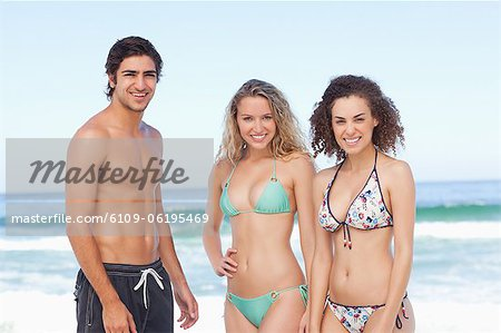 Three friends looking ahead while standing by the sea Stock Photo - Premium Royalty-Free, Image code: 6109-06195469