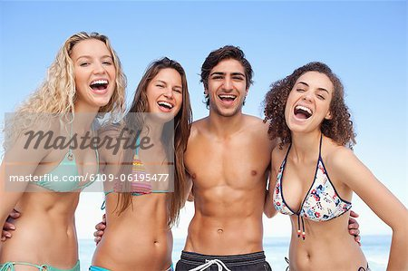Four friends laughing as they hold each other Stock Photo - Premium Royalty-Free, Image code: 6109-06195477