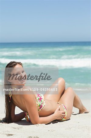 Woman looking behind her as she sunbathes Stock Photo - Premium Royalty-Free, Image code: 6109-06195603