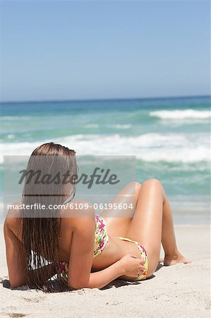 Woman looking towards the sea as she sunbathes on the sand Stock Photo - Premium Royalty-Free, Image code: 6109-06195604