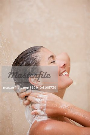 Side view of smiling woman washing her hair in the shower Stock Photo - Premium Royalty-Free, Image code: 6109-06195739