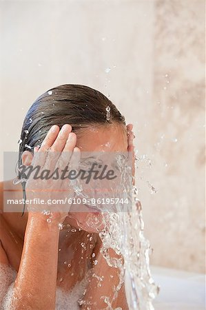 Woman in the tub washing her face Stock Photo - Premium Royalty-Free, Image code: 6109-06195744
