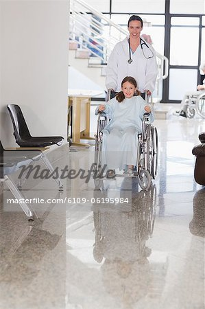 Smiling doctor wheeling a smiling girl in a wheelchair Stock Photo - Premium Royalty-Free, Image code: 6109-06195984