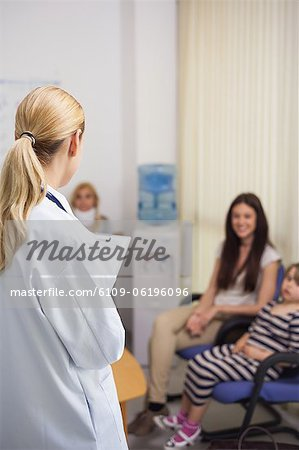 Blonde doctor talking to patient in a waiting room Stock Photo - Premium Royalty-Free, Image code: 6109-06196096