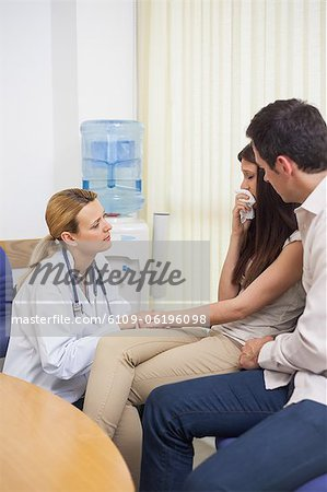 Doctor talking to a crying woman in a waiting room Stock Photo - Premium Royalty-Free, Image code: 6109-06196098