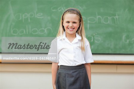 Girl standing in front of blackboard Stock Photo - Premium Royalty-Free, Image code: 6109-06196567