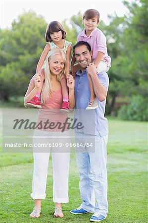 Portrait of parents giving children a piggy back Stock Photo - Premium Royalty-Free, Image code: 6109-06684764