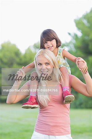Mother giving daughter a piggy back Stock Photo - Premium Royalty-Free, Image code: 6109-06684766