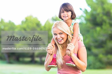 Beautiful mother giving daughter a piggy back Stock Photo - Premium Royalty-Free, Image code: 6109-06684767