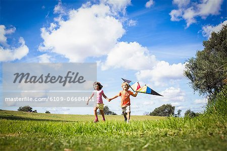 Brother and sister holding hands and playing with a kite Stock Photo - Premium Royalty-Free, Image code: 6109-06684811