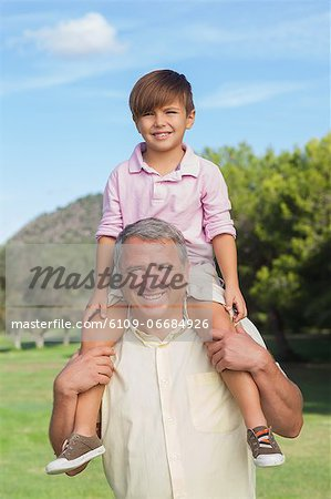 Grandfather giving grandson a piggy back Stock Photo - Premium Royalty-Free, Image code: 6109-06684926