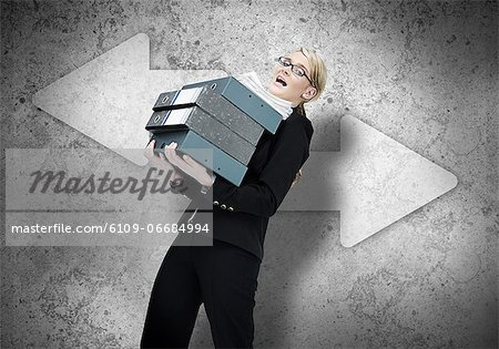 Woman struggling with work load Stock Photo - Premium Royalty-Free, Image code: 6109-06684994