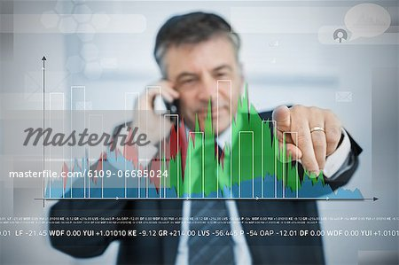 Businessman selecting point on large graph on touchscreen Stock Photo - Premium Royalty-Free, Image code: 6109-06685024
