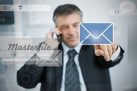 Businessman selecting email application on touchscreen Stock Photo - Premium Royalty-Free, Image code: 6109-06685025