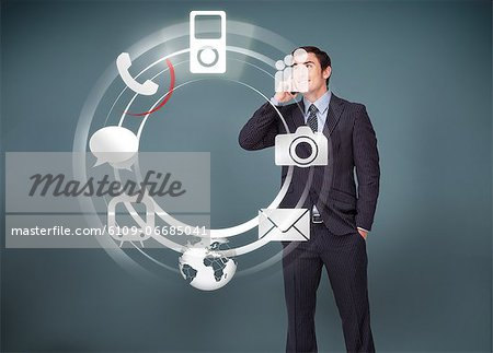 Businessman on the phone looking at wheel of applications Stock Photo - Premium Royalty-Free, Image code: 6109-06685041